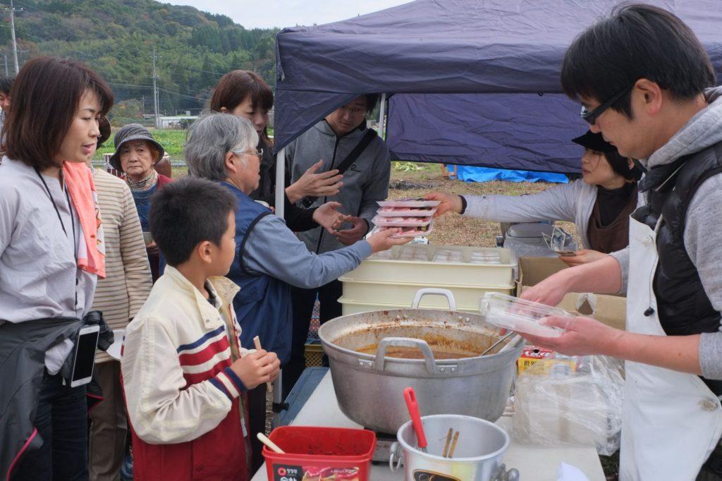 蒲池さん(右)の煮込み肉の振舞い